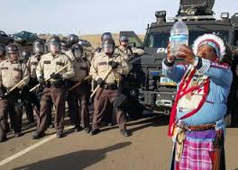 Water Protector praying with water in the face of militarized police in Standing Rock.